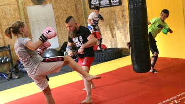 Jocelynn Harris, 11, throws a kick at Mixed Martial Arts fighter Cody Stevens, while at his gym in Madison Township on Thursday evening.