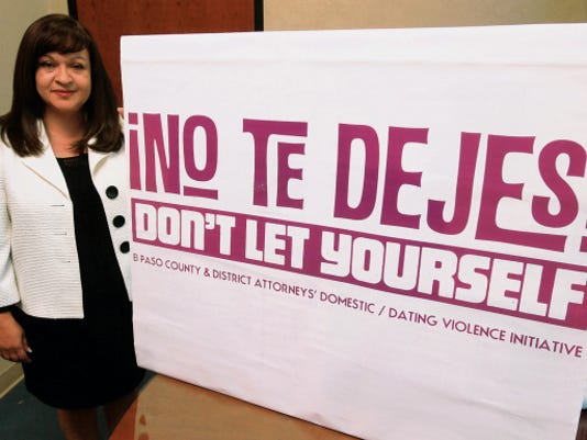 """VICTOR CALZADA-EL PASO TIMES El Paso County Attorney Jo Anne Bernal showed a """"No Te Dejes/Don't Let Yourself"""" campaign sign Thursday at her office. The county attorney and the district attorney's offices work together to stop domestic/dating violence."""