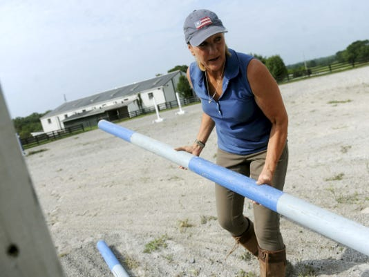 Holly Sands, a breast cancer survivor, readies some jumps before the start of teaching riding lessons at Stonewood Farms in Dover Township. Sands would work on the farm throughout her cancer treatment. She found the labor to be a distraction and a time to reflect on what was important in her life. (Jason Plotkin -- Daily Record/Sunday News)