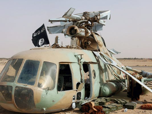 This photo released on May 31 by a militant website, which has been verified and is consistent with other AP reporting, shows a flag of the Islamic State group placed on a damaged helicopter at Tadmur military airbase, which was captured by the Islamic State group in Palmyra in Homs province, Syria.