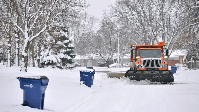 City of St. Cloud Public Works Department snowplow driver Todd Boettcher makes his way down residential streets, dodging garbage bins in the Centennial neighborhood Tuesday morning, Dec. 1.