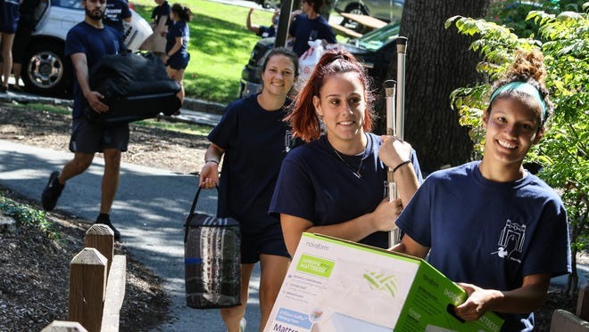 Soccer team Thalia Santacruz, far right, Brielle Castanheira, and Caroline Kelly unload freshman cars during the Move-in day at Drew University on August 24, 2017.  Alexandra Pais/ The Daily Record