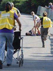 Medical personnel rush to help runner William Duggan