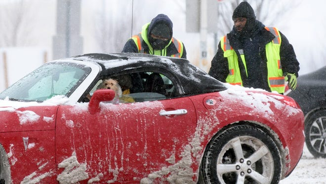 A dog is seen in the driver's seat as two men help free a car stuck near the entrance to the Ben Franklin Bridge as a 'cyclone bomb' brings snowfall in in Camden, N.J Jan. 4, 2018.