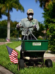 A landscaper spreads granulated fertilizer on a lawn