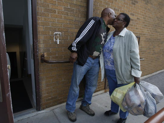 Carolyn Bailey, church member at Baber AME Church in Rochester, delivers donated bread to the church on June 18, 2015. She's greeted at the door with a hello hug from George Larkin, who's a minister at the church.