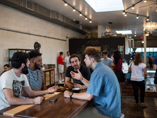 Customers converse at Reve Coffee Roasters in downtown
