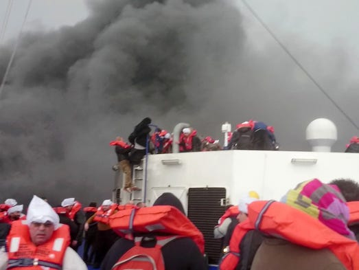 Passengers wait to be rescued after the car ferry