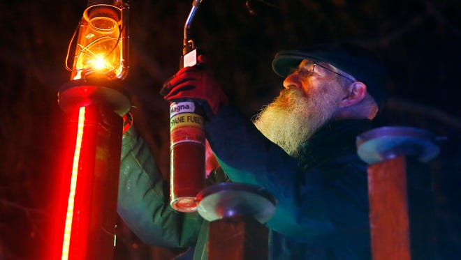 The annual Menorah lighting on the Morristown Green. Reuven Tarlow, a building engineer from the Rabbinical College of America in Morris Township lights the shamash as he helps Norman Feinstein, Principal, Vice Chairman, Fund Manager of The Hampshire to light the two lamps of Chanukah on the Green. December 13, 2017. Morristown, New Jersey
