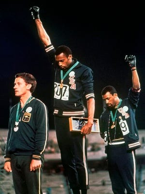 From Oct. 16, 1968, extending gloved hands skyward in racial protest, U.S. athletes Tommie Smith, center, and John Carlos stare downward during the playing of national anthem after Smith received the gold and Carlos the bronze for the 200 meter run at the Summer Olympic Games in Mexico City. Australian silver medalist Peter Norman is at left. The U.S. Olympic and Paralympic Committee is signaling willingness to challenge longstanding IOC rules restricting protests at the Olympics, while also facing backlash from some of its own athletes for moves viewed by some as not being driven by sufficient athlete input.
