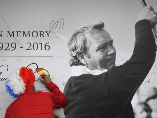 A fan signs a memorial wall tribute to Arnold Palmer during a practice round Wednesday for the Ryder Cup golf tournament at Hazeltine National Golf Club in Chaska.