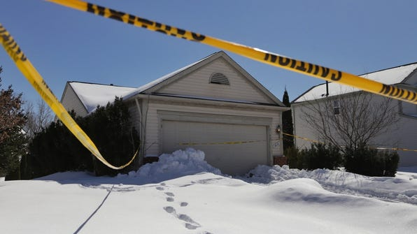 Police tape surrounds the Pontiac, Mich., house March 6, 2014, where a woman in her 40s was found dead in the back seat of her SUV in her garage. They say she may have been there as long as six years.
