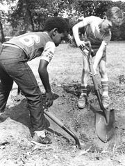 Digging a hole for the fire at this Camp Fire file photo from June 9, 1984, are Deith Taylor, left, and Robert Mansfield, and making a s'more is Jana Tucker.