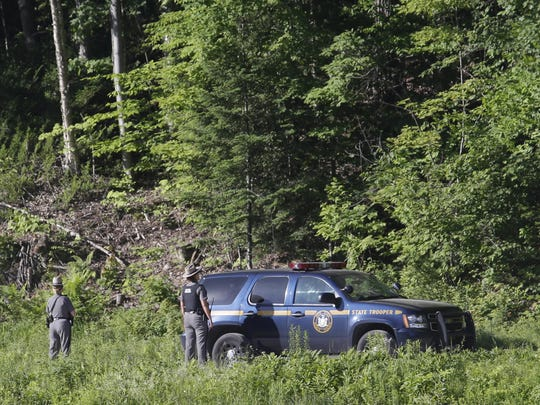New York State Police officers search Saturday in a wooded area in Malone, N.Y.