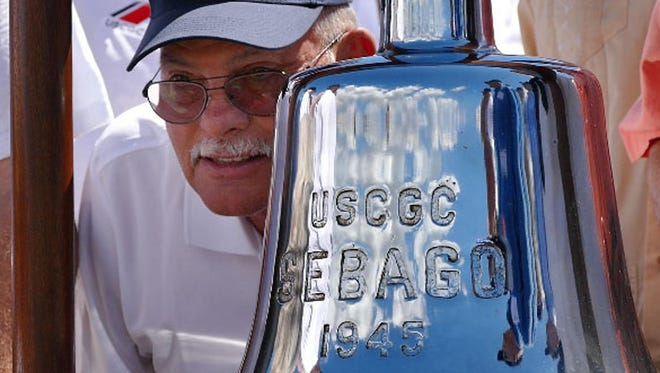 One of the former crew members of the long retired Coast Guard Cutter Sebago poses next to the ships bell during a group photo of former crewmembers on hand for the unveiling a plaque honoring the ship and her crew Saturday morning at Plaza de Luna.