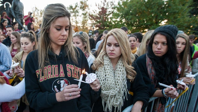 TALLAHASSEE, FL- NOVEMBER 20: Florida State University student Colleen Rick (L) from Jupiter, Florida passes the flame to her fellow students during the Gathering of Unity candlelight vigil on campus after the shooting of three FSU students earlier in the day on November 20, 2014 in Tallahassee, Florida. About 3,000 students attended the vigil according to FSU Police Chief David Perry. (Photo by Mark Wallheiser/Getty Images)
