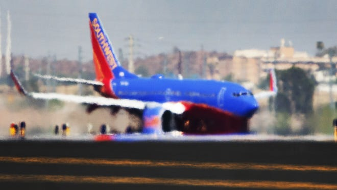 The right engine of a Southwest Airlines 737 appears to melt off the wing from the mirage of heat rising from the runway as it lands at Sky Harbor International Airport as the temperature hit 119 degrees, Tuesday, June 20, 2017.