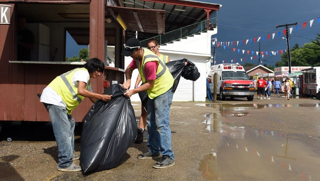 Jerry Baker, of Trinway, Aaron Veyron and Courtney Coen, both of Zanesville, empty trash bins throughout the fairgrounds during the Muskingum County Fair.