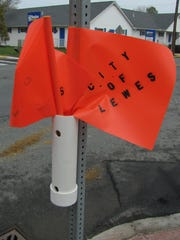 A pilot program in Lewes has been implemented in which pedestrians can use flags to cross busy intersections along Savannah Road to alert motorists.