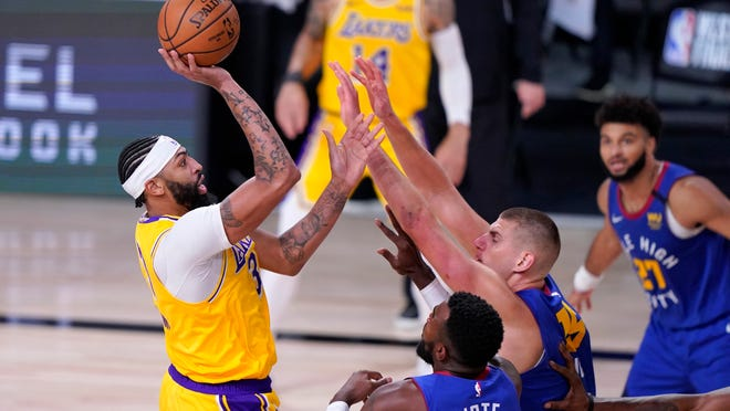Los Angeles Lakers forward Anthony Davis, left, attempts a shot over Denver Nuggets' Paul Millsap, bottom front, Nikola Jokic, bottom center, and Jamal Murray (27) during the second half an NBA conference final playoff basketball game, Friday, Sept. 18, 2020, in Lake Buena Vista, Fla. (AP Photo/Mark J. Terrill)