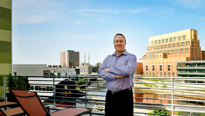 Pat Gillespie of The Gillespie Group poses for a photo on the balcony of his Marketplace Apartments in the Stadium District in downtown Lansing, Friday morning, May 25, 2018.