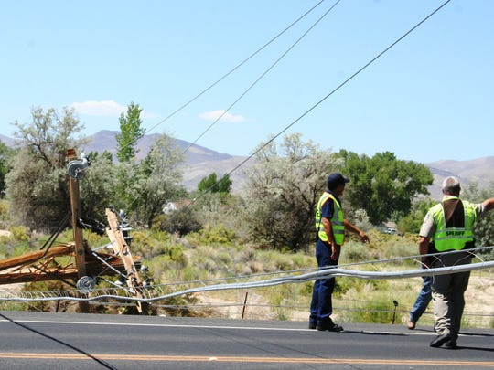 Fire and sheriff's office personnel look at the downed power poles that resulted Wednesday morning on Nevada 95A in Yerington after a semi-trailer rig snagged some lines, breaking at least three power poles, including this one at the 95A and Green Acres Lane intersection, where lines crossed the roadway.