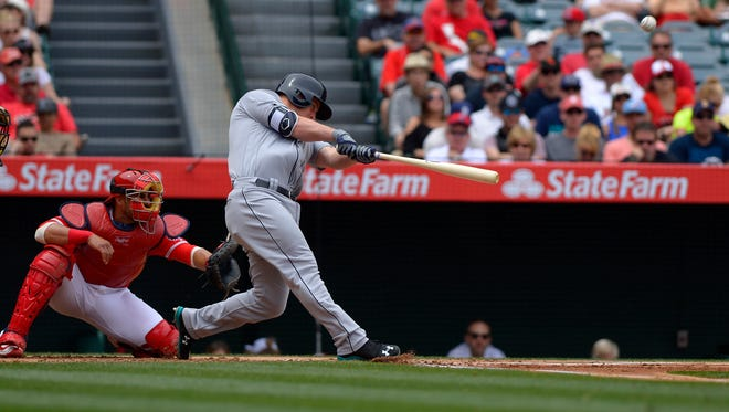 Seattle Mariners' Kyle Seager, right, hits a three-run home run as Los Angeles Angels catcher Geovany Soto watches during the first inning of a baseball game, Sunday, April 24, 2016, in Anaheim, Calif. (AP Photo/Mark J. Terrill)