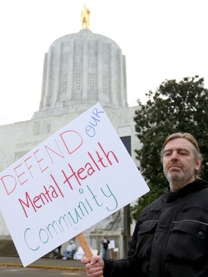 Jens Nelson, a Salem adult foster care provider, protests a contract negotiated on providers' behalf by SEIU that they say will cut their reimbursement for caring for mental health clients by up to 60 percent at the Oregon State Capitol in Salem on Tuesday, Dec. 1, 2015.