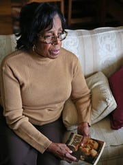 """From her home in Gary, IN, Tuesday, October 6, 2015, Senator Earline Rogers talks about her experiences with Paula Cooper and legislation around her case.  She shows her autographed copy of """"Dead Man Walking,"""" by Sister Helen Prejean."""