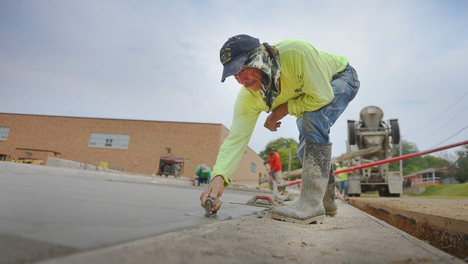 Roberto Martinez, Dokotaland Concrete, lays out the concrete at Garfield Elementary School for a new playground Wednesday in Sioux Falls.