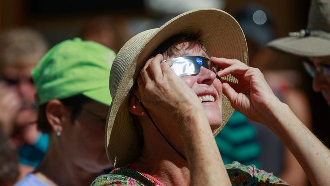 Spectators look at the eclipse through a protective eye-wear Monday during a viewing event at the Aztec Ruins National Monument in Aztec, N.M.