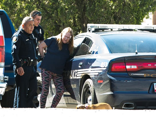 A woman is handcuffed and placed in the back of a Las