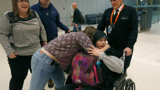 Courtney Wagner arrives with her mother, Jamie, left, as her stepfather Barry Clark watches her get a hug from her sister, Allie, at the Greater Rochester International Airport.