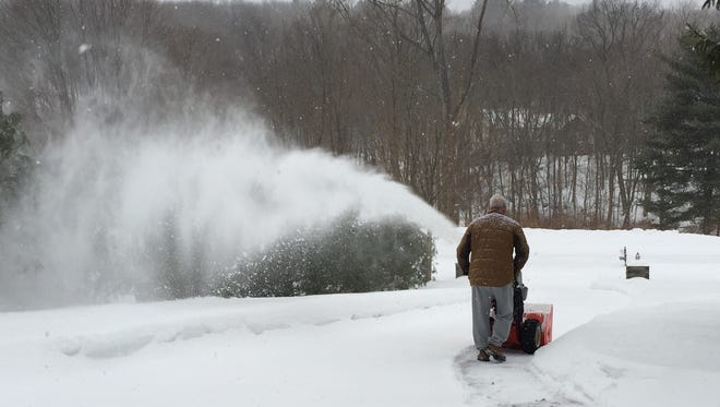 Homeowner snow blows his driveway in Brewster as a wintry mix falls Monday morning.