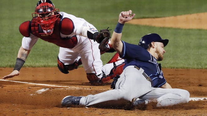 The Tampa Bay Rays' Michael Brosseau, right, evades the tag from Boston Red Sox's Christian Vazquez as he scores on a single by Yandy Diaz during the third inning of Tuesday's game in Boston.