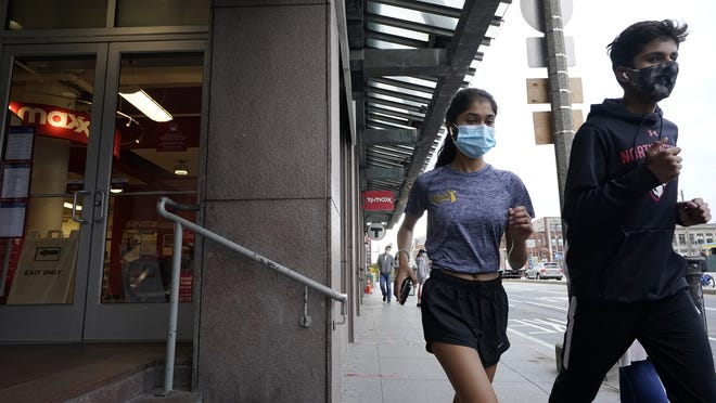 Runners wear masks out of concern for the coronavirus while jogging along a sidewalk, Tuesday, Oct. 27  in Boston.