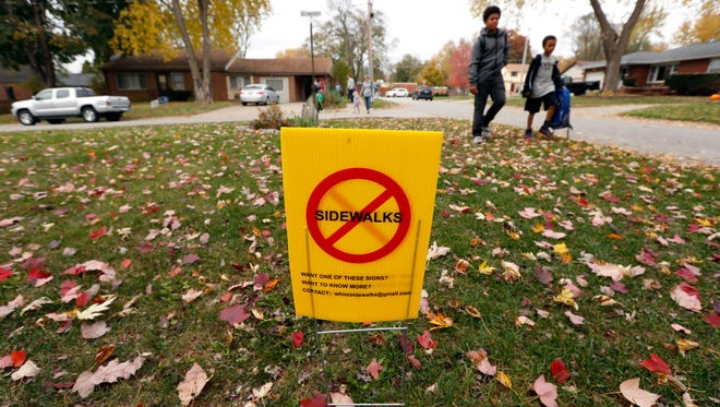 Students walk past a sign protesting sidewalks in Windsor Heights last fall.