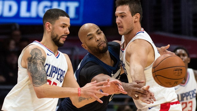 Minnesota Timberwolves forward Taj Gibson, center, tries to intercept a pass intended for Los Angeles Clippers guard Austin Rivers, left, during the second half of an NBA basketball game Wednesday, Dec. 6, in Los Angeles. The Timberwolves won 113-107.
