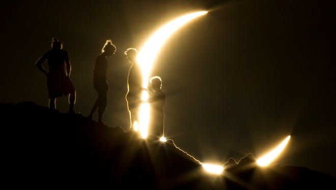 Hikers watch a partial solar eclipse from Papago Park in Phoenix May 20, 2012. The moon's silhouette blocked out about 83% of the sun's surface area in the Phoenix area. Southeastern Michigan is expected to see about 80% of the total solar eclipse on Aug. 21, 2017.