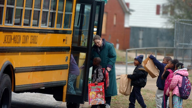 Lincoln Elementary School librarian Sandra Hobbs helps students onto a school bus in this 2011 file photo.