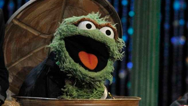 Oscar the Grouch in his trash can.