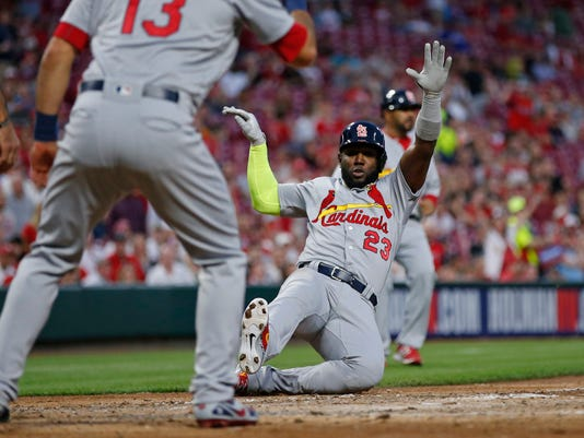 St. Louis Cardinals' Marcell Ozuna (23) scores on a single by Yadier Molina during the sixth inning of a baseball game against the Cincinnati Reds, Friday, April 13, 2018, in Cincinnati. (AP Photo/Gary Landers)