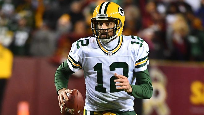 Green Bay Packers quarterback Aaron Rodgers (12) rolls out against the Washington Redskins during the first half at FedEx Field.