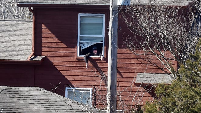 Jerry Dean Hopper Jr. looks out of a window from a house behind Hopper's Dinner Club on Thursday. Officers took Hopper, 41, into custody after an armed standoff which lasted more than an hour.