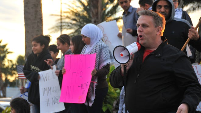 Pastor Joel Tooley with First Church of the Nazarene in Melbourne speaks to the crowd. Protesters gather Sunday evening at Exploration Tower at Port Canaveral to protest Donald Trump's immigration order.