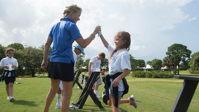 """The First Tee of the Treasure Coast instructor MaryLois Altmann (left) congratulates Abygail Armstrong, 7, of Port St. Lucie, during their weekly golf session on Thursday at Monarch Country Club in Palm City. The group brings kids from the Boys & Girls Clubs of Martin County together at different area golf courses to learn golf basics and life lessons, like Thursday's session on sportsmanship and perseverance. """"I feel like a million bucks,"""" said Altmann. """"I feel like I'm actually making a difference. These kids trust me."""""""