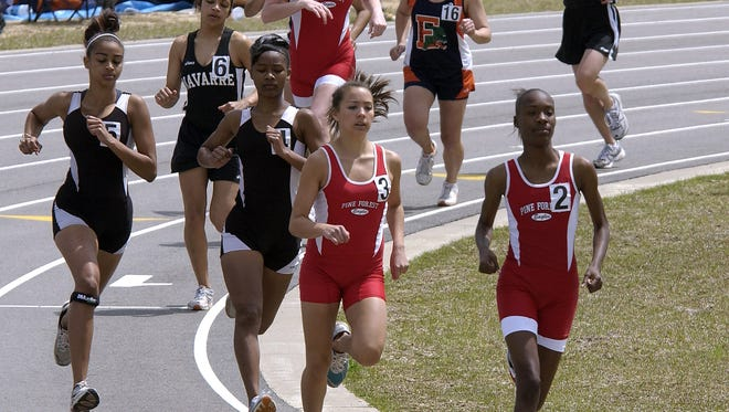 Pine Forest's Darroneshia Lott leads the 1,600-meter race during the 2014 EscaRosa County Track and Field Championship at West Florida High.