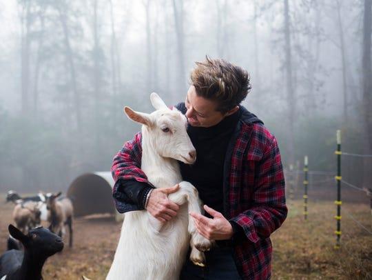 Dairy goat farm hand, Sandra Coffman, hugs a Saanen