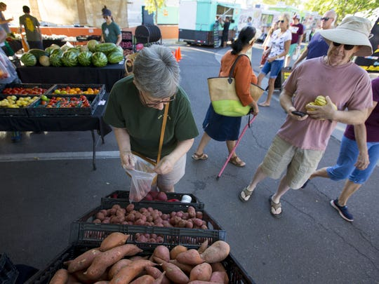 Mary Weinreber, from Gold Canyon,  looks for potatoes from Crooked Sky Farms, during the Gilbert Farmers Market.