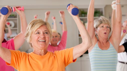 Seniors exercising with dumbbells in a health club.